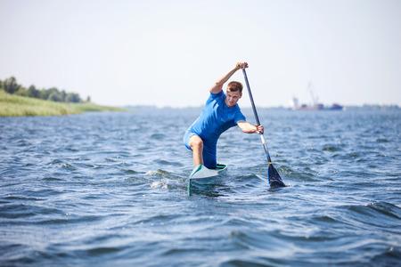 Photo pour Young man rowing in canoe along a river - image libre de droit