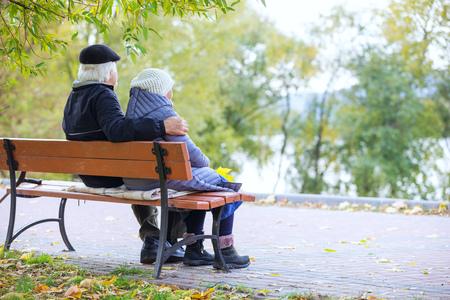Foto de Senior couple sitting on bench in autumn park - Imagen libre de derechos