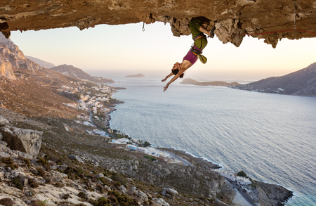 Photo pour Female rock climber hanging upside down on challenging route in cave at sunset, resting before keeping on her attempt - image libre de droit