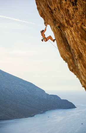 Photo pour Caucasian young woman in bikini climbing challenging route on overhanging cliff - image libre de droit