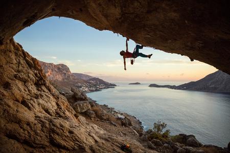 Photo pour Caucasian man climbing challenging route in cave, against beautiful evening view - image libre de droit