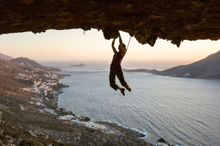 Female rock climber on challenging route in cave at sunset, Kalymnos, Greece