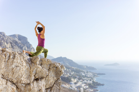 Photo pour Young Caucasian woman practicing yoga or working out while standing on cliff on sea coast - image libre de droit