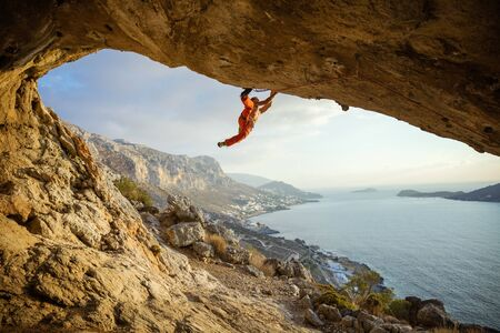 Photo pour Young man climbing challenging route in cave against beautiful view of coast - image libre de droit