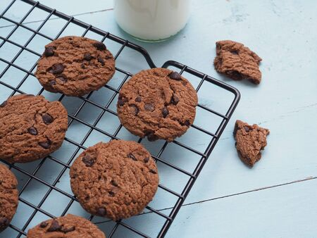 Photo pour Homemade double chocolate chip cookies on a wire rack over blue wooden background, fresh from the oven, copy space. - image libre de droit