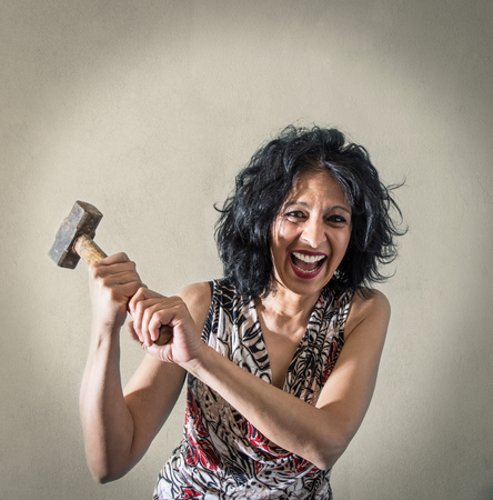 a Woman screaming with in hand a hammer
