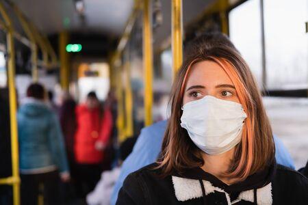 Photo pour Young female adult commutes in a protective face mask. Coronavirus, COVID-19 spread prevention concept, responsible social behaviour of a citizen - image libre de droit