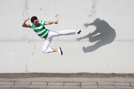 man fighting against his own shadow