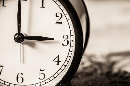 Retro vintage clock on sack closeup at 3 o'clock