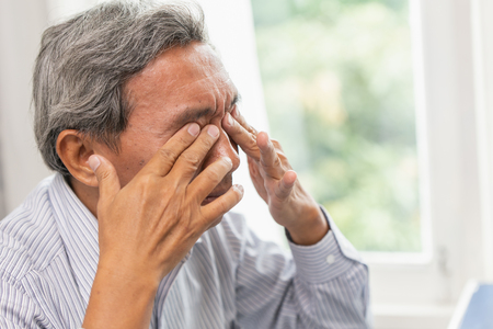 Photo pour Asian Elderly Self Eye Soothing Massage from irritation problem fatigue and tired after hard work or computer vision syndrome - image libre de droit