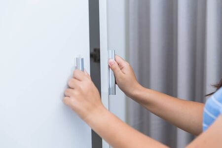 Photo pour Closeup Girl Hand Open Wardrobe or Cupboard Door. - image libre de droit