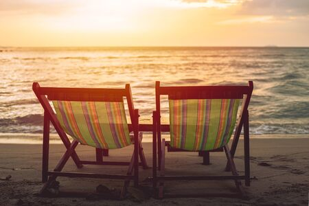 Photo for two blank beach bed chair set on the beach with sun twilight sky background. - Royalty Free Image