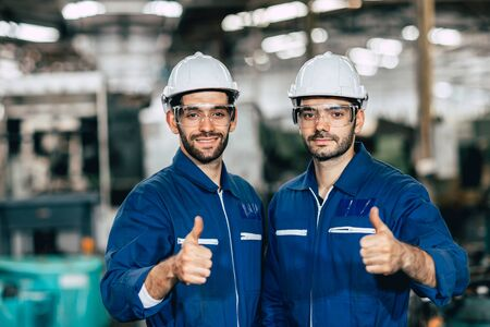Photo pour Happy worker team smiling hand show thumb up for good working in factory. - image libre de droit