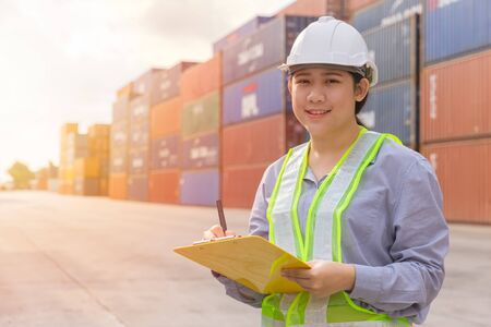 Photo pour Asian young teen happy worker checking stock in shipping port work manage import export cargo containers. - image libre de droit