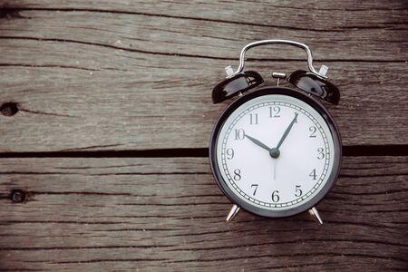 Foto de old clock place on wooden background with space for text for times memory concept. - Imagen libre de derechos