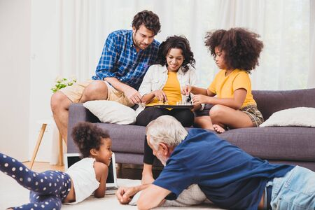 Photo pour Lovely home family stay together in living room father mother and grandfather playing with daughter mix race. - image libre de droit