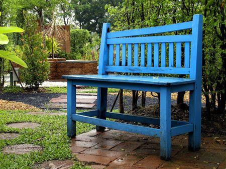 A wet blue chair in the garden