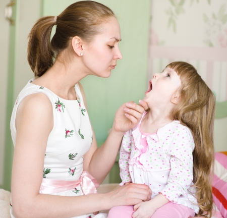 young mother examining little girl s throat