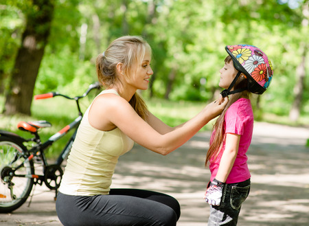 Photo for young mother dresses her daughter s bicycle helmet - Royalty Free Image