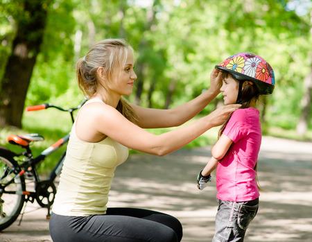 Photo pour young mother dresses her daughter s bicycle helmet - image libre de droit