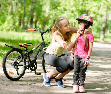 young mother dresses her daughter\'s bicycle helmet