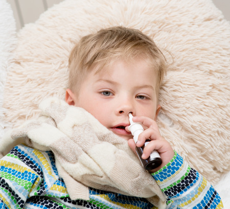 ill boy with flu at home using nose spray