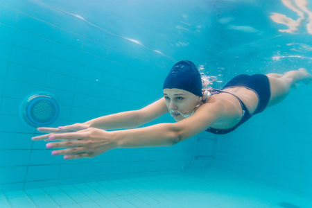 Woman swimming underwater in pool.