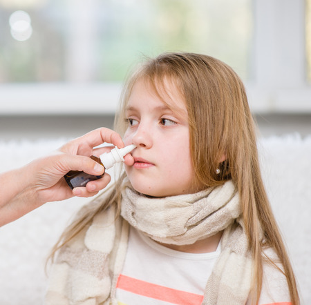 Mother using nose spray to cure her teen girl.