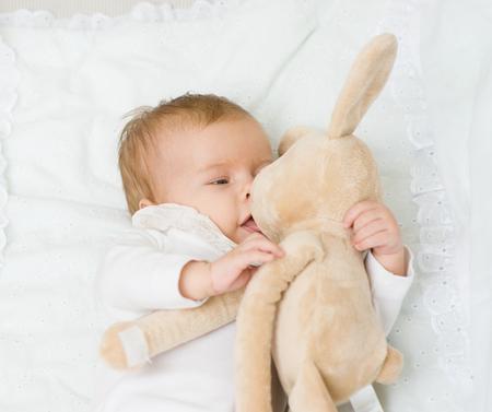 Happy newborn baby plays with toy rabbit.