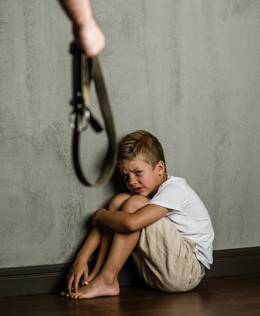 Domestic violence: Man's hands with belt and frightened beaten son.