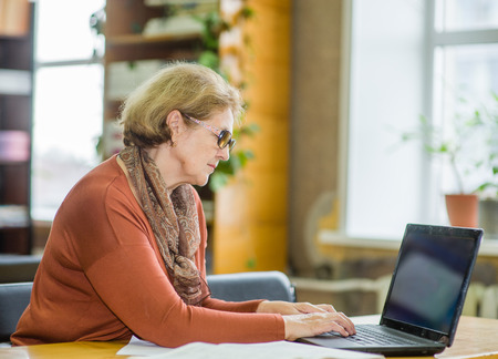 Elderly lady working with laptop in library.