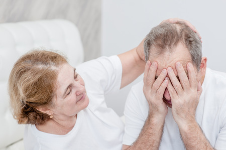 elderly wife calms a crying husband at bedroom.