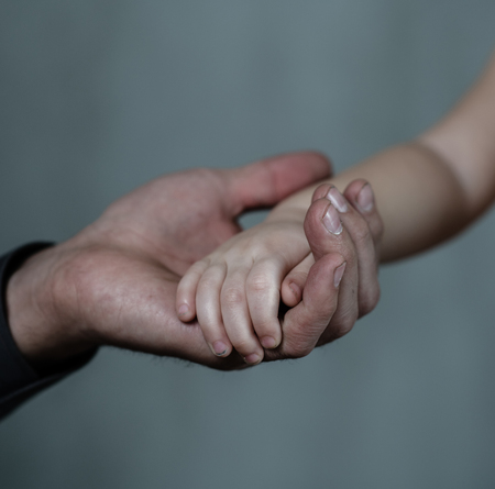 Photo for Closeup senior man and baby girl holding hands together on dark background. - Royalty Free Image