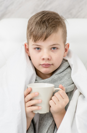 Photo pour Sick boy  with warm scarf sitting on the bed and holds cup. - image libre de droit