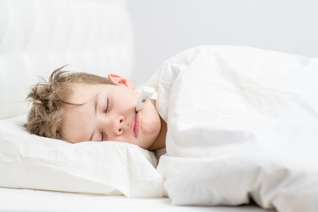 Photo for Sick boy sleep under blanket with thermometer in his mouth. - Royalty Free Image