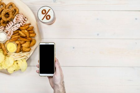 Photo pour Varied snacks and beer with percent sign on a beer foam, and smartpnone in male hand on light wooden background. Internet delivery concept. Top view. Empty space for text. - image libre de droit