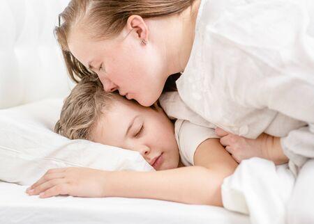 Photo pour Mother kisses young boy before bedtime. - image libre de droit