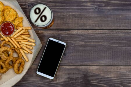 Photo pour Varied snacks and beer with percent sign on a beer foam and smartpnone on dark wooden background. Internet delivery concept. Top view. Empty space for text. - image libre de droit