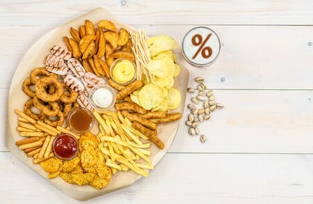 Foto de Mix of snacks and beer with percent sign on a beer foam on light wooden background. Top view. Empty space for text. - Imagen libre de derechos