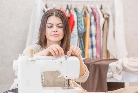 Photo pour Young woman seamstress sitting and sews on sewing machine. Hobby sewing as a small business concept. - image libre de droit
