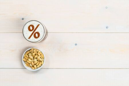 Photo pour Beer ith percent sign on a beer foam and peanut on light wooden background. Empty space for text. - image libre de droit