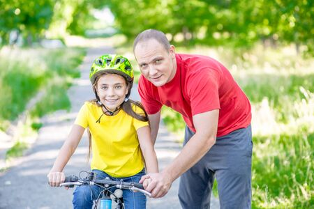 Photo pour Smiling father teaches his daughter to ride a bicycle in the park. - image libre de droit