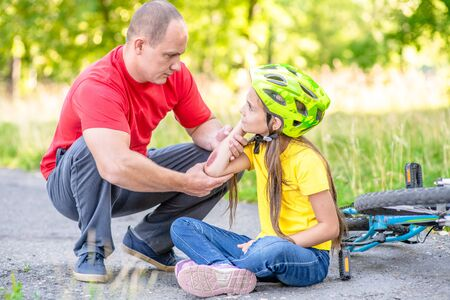 Photo for Father looks at the wound of his daughter, who fell from a bicycle. - Royalty Free Image