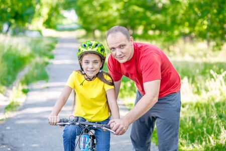 Photo pour Happy family. Father teaches his daughter to ride a bicycle in the summer park. - image libre de droit