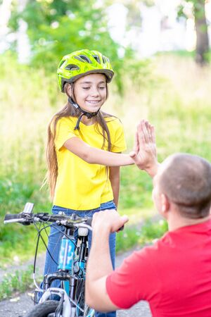 Photo pour Father and daughter give high five while cycling in the park. - image libre de droit