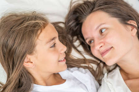 Photo for Happy family at home. Young woman lies with her little daughter on the bed before bedtime - Royalty Free Image