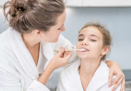 Photo pour Happy family at home. Young mother teaches her cute daughter how to brush teeth with toothbrush. - image libre de droit