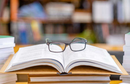 Photo for Eyeglasses lies on open book in a library. - Royalty Free Image