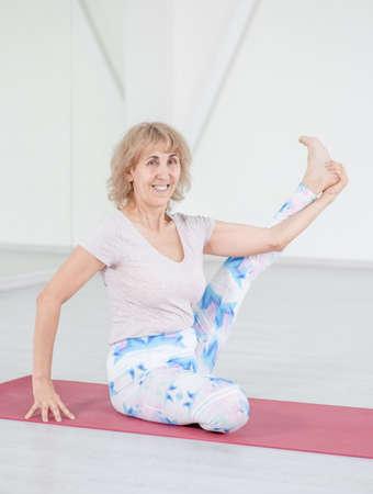 Photo pour Senior woman stretches legs in a yoga studio. Sport healthy concept. - image libre de droit