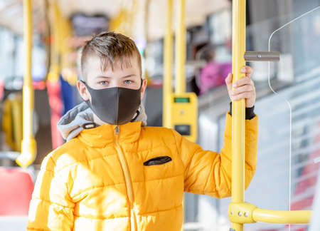 Photo pour Young boy wearing protective mask holding on to the handrail in the bus. - image libre de droit